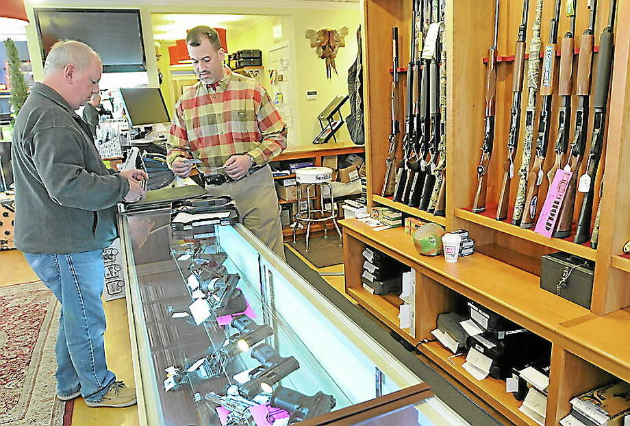 Thomas Powers of Branford, left, shows his pistol permit to Mike Higgins,  co-owner of TGS Outdoors on Main Street in Branford, Conn. as they start the required Federal and State of Connecticut paperwork before he purchases a handgun there Tuesday April 2, 2013.  Photo by Peter Hvizdak / New Haven Register. Photo: New Haven Register / ©Peter Hvizdak /  New Haven Register