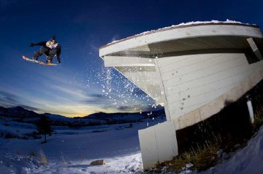 Snowboarder Joe Mack grabs tail on a bomb drop in Park City, Utah.