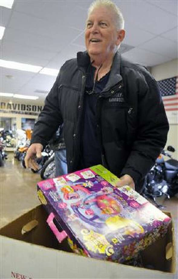 Jack Lewis laughs as he donates to Toy for Tots during the charity turkey fry in Greeley, Colo. Photo: AP / The Greeley Tribune