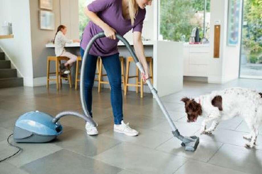 Woman vacuuming around sleeping dog Photo: Getty Images/Caiaimage / Caiaimage