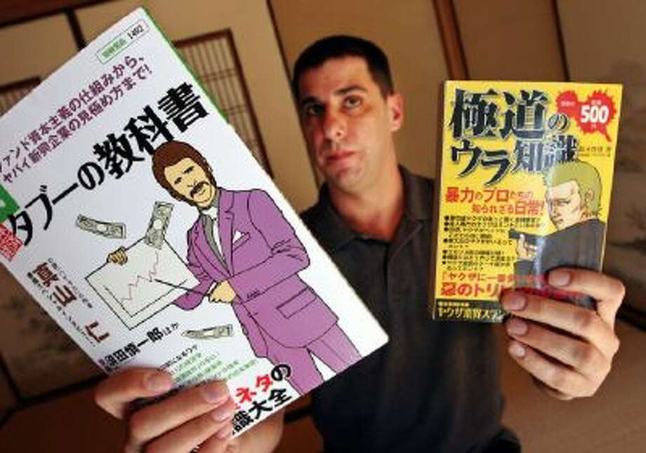 This photo taken on March 20, 2009 shows Jake Adelstein, a former Yomiuri Shimbun daily crime reporter and an expert and author on the yakuza, Japanese crime syndicates, holds up manga (cartoon) magazines based on the yakuza and a business management book written by a former crime boss.