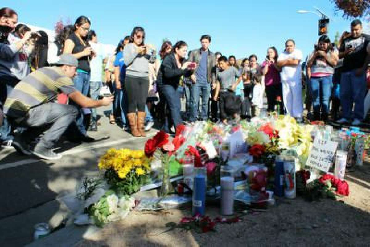 People gather at the roadside memorial for actor Paul Walker in Valencia, Calif. on Sunday, Dec. 1, 2013. Walker is believed to have been a passenger in the car that crashed and burned on Saturday, Nov. 30, 2013 as a charity event at a nearby car shop was winding down.