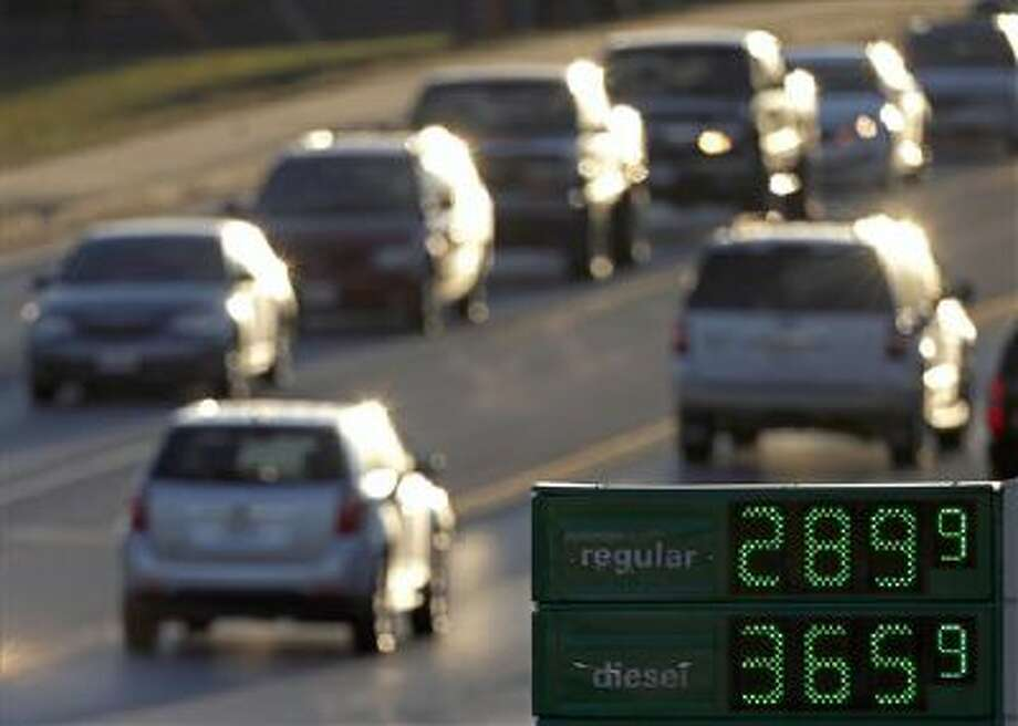 Motorists drive past a gas station selling regular unleaded gasoline for less than $3 a gallon in Independence, Mo. The average price of gasoline has tumbled 49 cents from their peak this year to $3.29 a gallon, putting shoppers on track to have the lowest prices at the pump since 2010, according to AAA. Photo: AP / AP