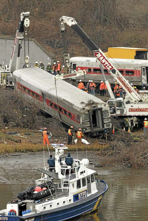 """Cranes salvage the last car from from a train derailment in the Bronx, N.Y., on Monday. Federal authorities began righting the cars Monday morning as they started an exhaustive investigation into what caused a Metro-North commuter train rounding a riverside curve to derail, killing four people and injuring more than 60 others. A second """"event recorder"""" retrieved from the train may provide information on the speed of the train, how the brakes were applied, and the throttle setting, a member of the National Transportation Safety Board said Monday. (AP Photo/Mark Lennihan) Photo: AP / AP"""