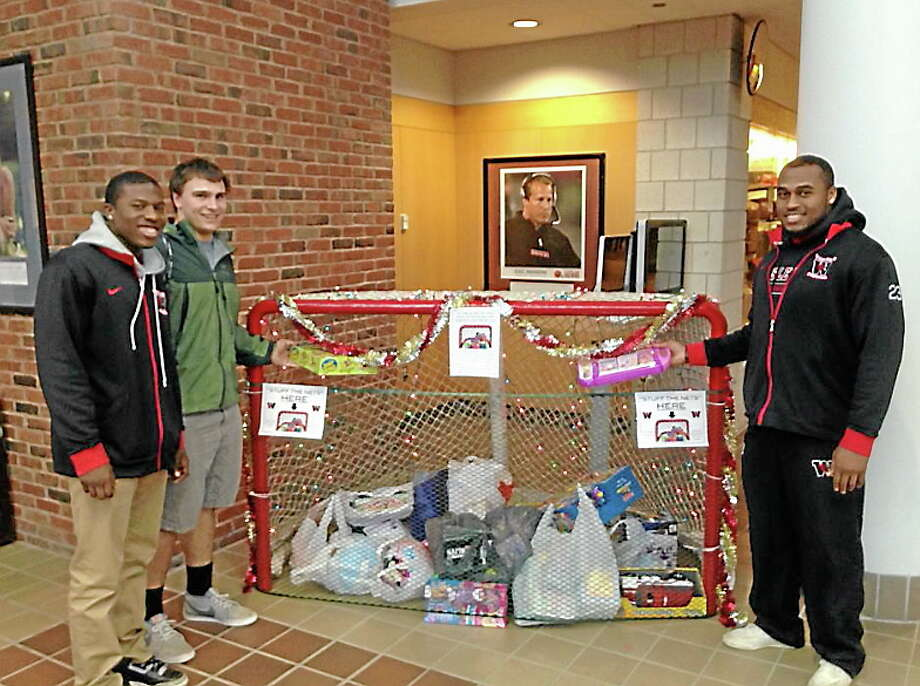 Wesleyan football players pose with the hockey net of toys from last year's Stuff the Nets for Macdonough School. Photo: Submitted Photo
