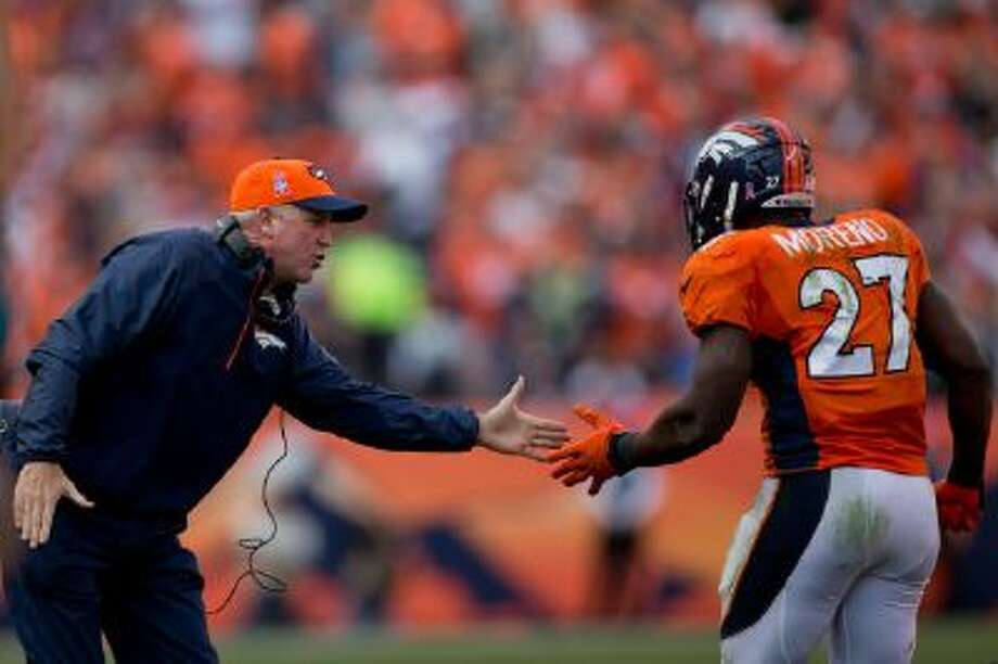 Head coach John Fox of the Denver Broncos celebrates with running back Knowshon Moreno #27 after he scored a third quarter touchdown against the Jacksonville Jaguars at Sports Authority Field Field at Mile High on October 13, 2013 in Denver, Colorado. The Broncos defeated the Jaguars 35-19.
