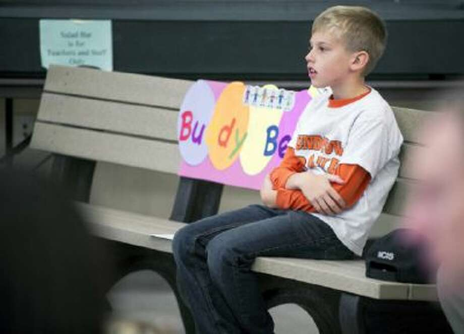 "Christian Buck, a second-grader at Roundtown Elementary School in York, Pa., sits on his ""Buddy Bench."""