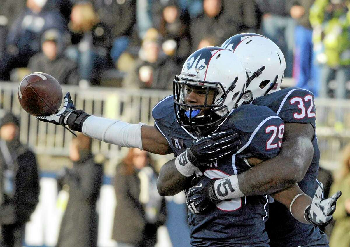 UConn cornerback Taylor Mack (29) and linebacker Jefferson Ashiru (32) celebrate after Mack intercepted a pass during Saturday's game against Rutgers.