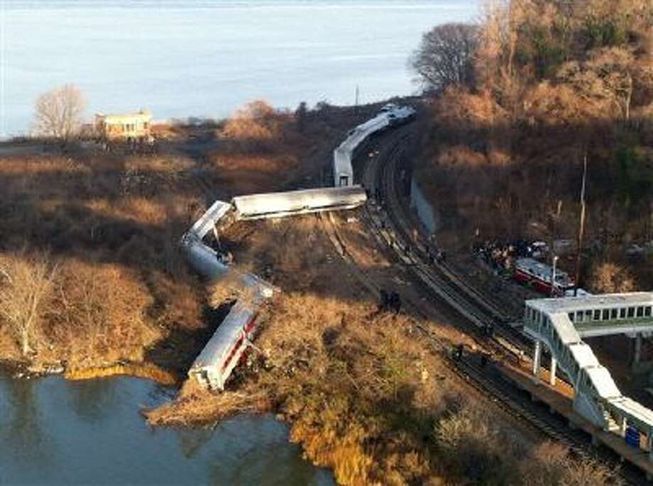 """Cars from a Metro-North passenger train are scattered after the train derailed in the Bronx neighborhood of New York, Sunday, Dec. 1, 2013. The Fire Department of New York says there are """"multiple injuries"""" in the train derailment, and 130 firefighters are on the scene. Metropolitan Transportation Authority police say the train derailed near the Spuyten Duyvil station. (AP Photo/Edwin Valero) Photo: ASSOCIATED PRESS / AP2013"""