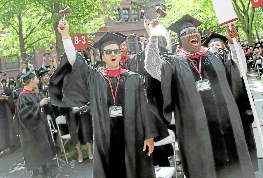 Adam Derry, left, and Jordan Christopher Wall, right, lead the cheers from students graduating from Harvard University's School of Law during commencement ceremonies in Cambridge, Mass., Thursday, May 30, 2013. Photo: Elise Amendola — The Associated Press  / AP