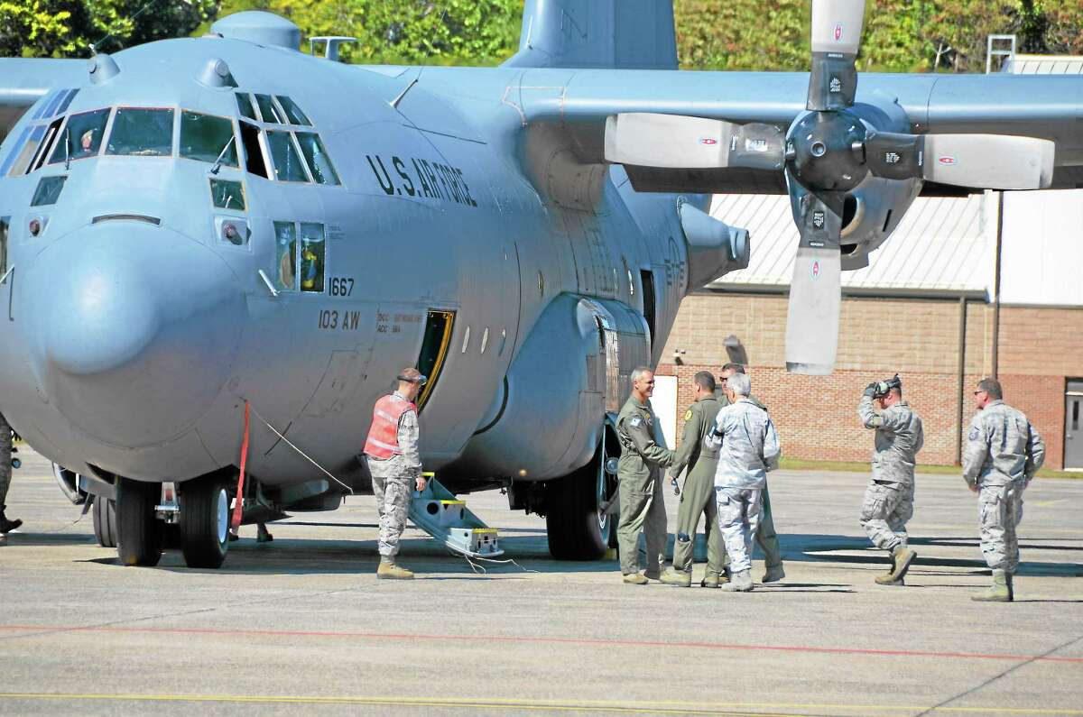 Airmen of the 103rd Airlift Wing welcome the first of eight C-130H aircraft expected to be assigned to the Connecticut Air National Guard moments after it touched down at Bradley International Airport, Windsor Locks, Conn., Tuesday, Sept. 24, 2013.
