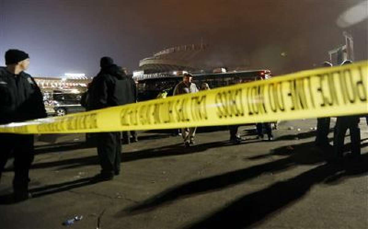 Kansas City, Mo. police work a crime scene in parking lot A outside Arrowhead Stadium, in Kansas City, Mo., after a person was killed Sunday, Dec. 1, 2013. Police Chief Darryl Forte said the death is being investigated as a homicide and that two suspects are in custody.