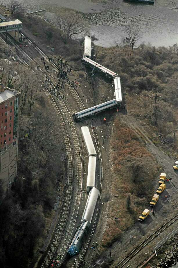 A Metro-North passenger train lays on it's side after derailing in the Bronx borough of New York, Sunday, Dec. 1, 2013. The train derailed on a curved section of track on Sunday morning, coming to rest just inches from the water and causing multiple fatalities and dozens of injuries, authorities said. Metropolitan Transportation Authority police say the train derailed near the Spuyten Duyvil station. (AP Photo/Mark Lennihan) Photo: AP / AP