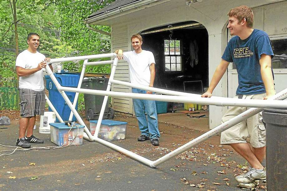 """Alex Gecan - The Middletown PressLeft to right, John Palmer, Eric Rosendahl and Steve Reitsma of the Channel Four News Team brace a """"dry fit"""" of framework for a glider they will fly in the Sept. 21 National Red Bull Flugtag. Photo: Journal Register Co."""
