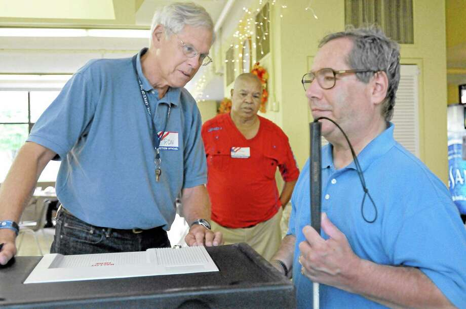 Poll workers Ron Klattenberg, left, and Tony Gaunichaux, center, assist Middletown resident Marty Knight deposit his paper ballot into the voting machine at the Middletown Senior Center. Democrats held a  primary Tuesday evening for Planning & Zoning. Knight is blind and uses the Accessible Voting System to vote in elections and primaries. Catherine Avalone — The Middletown Press Photo: Journal Register Co. / TheMiddletownPress