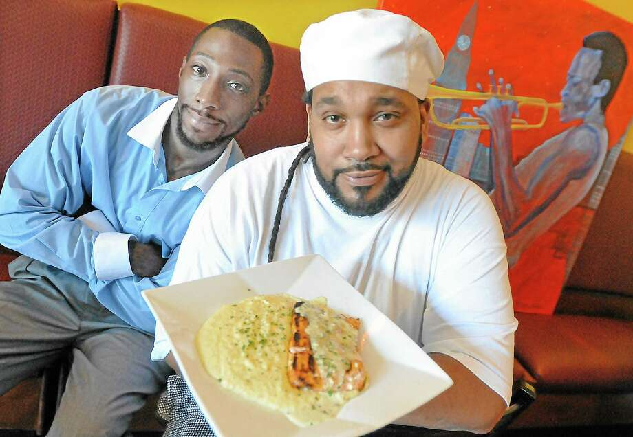 Guana Williams, right, owner of Scatz Restaurant and Jazz Lounge at 139 Main St. Ext. in Middletown, serves up a dish of salmon and grits with lemon butter sauce. At left is manager Kuron Johnson. Catherine Avalone — The Middletown Press Photo: Journal Register Co. / TheMiddletownPress
