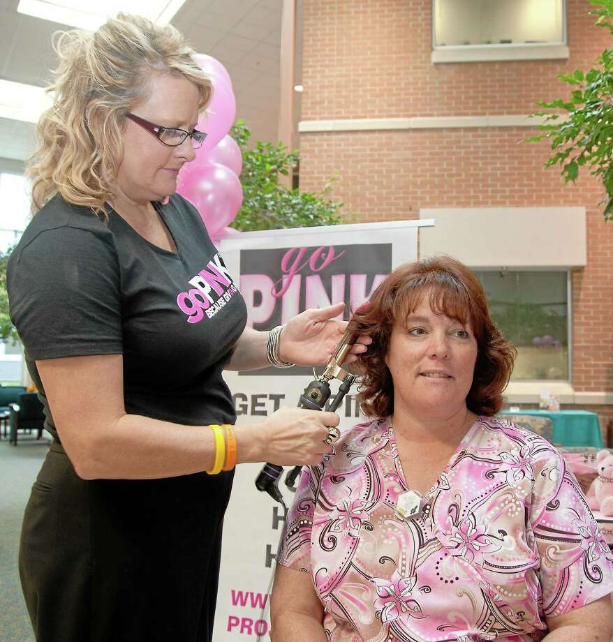 Georgi Marino, left, co-owner of EG Salon, puts the finishing touches on a pink hair extension for Middlesex Hospital Outpatient Center mammography technologist, Laura Daniels, during last year's goPINK fundraiser. (Middletown Press file photo) Photo: John Giammatteo / ©John Giammatteo 2012