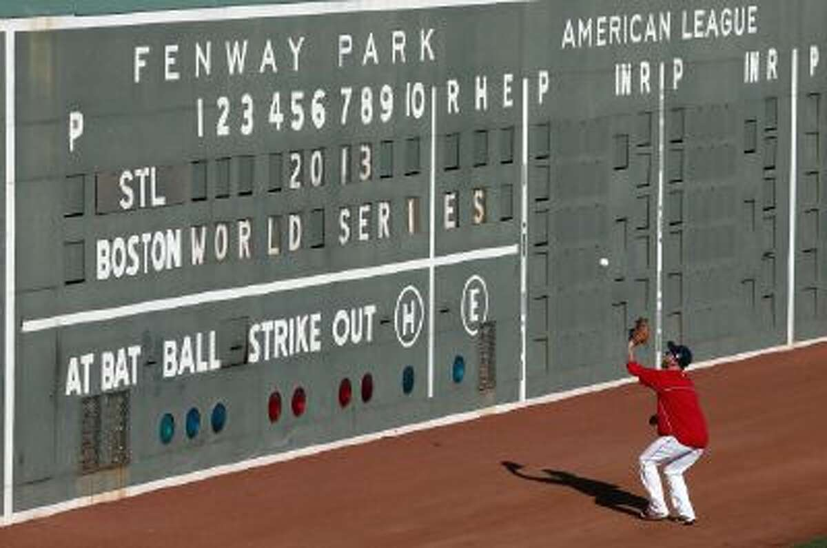 Boston Red Sox left fielder Mike Carp plays a ball hit off the Green Monster wall during baseball team practice at Fenway Park in Boston, Monday, Oct. 21, 2013.