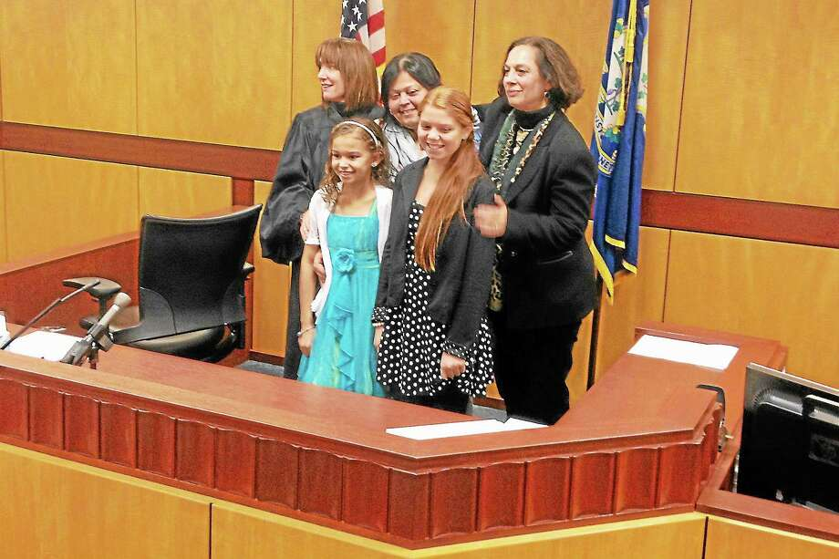 Frankie, 10, in the front left, with her older sister, Olivia, 11, in court Fridayv as their foster mother, Daisy Lopez, became their adoptive mother. Judge Bernadette Conway, back left, presided, and Department of Children and Families Commissioner Joette Katz, back right, congratulated the new family. Photo: Alex Gecan - The Middletown Press
