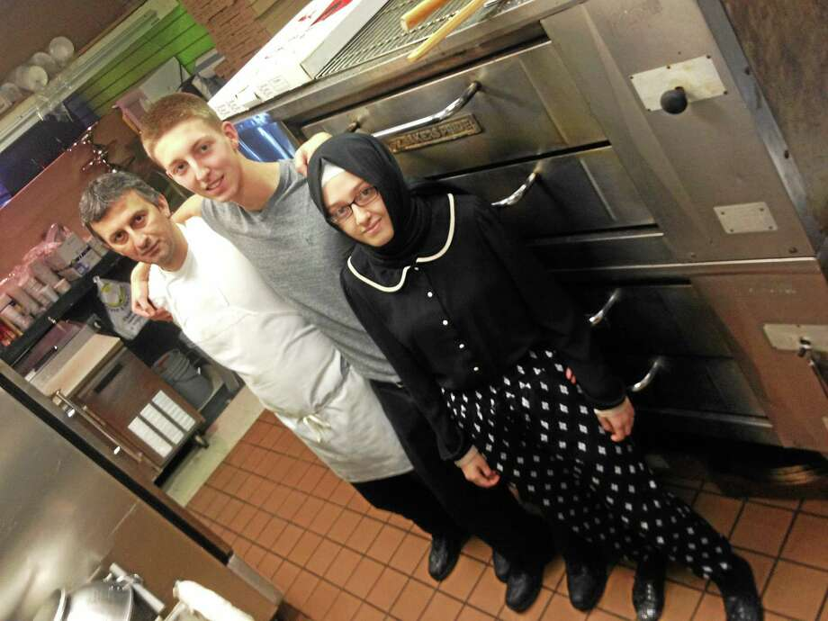 Ismail Topal, left, with his son, Mehmet, and daughter, Merve, in the kitchen of Cardinal Pizza, which he opened in December. Photo: Alex Gecan - The Middletown Press