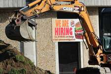 An excavator moves a pile of dirt at the construction site of the Burger King on Federal Road in Brookfield, Conn., on Thursday, Aug. 17, 2017.