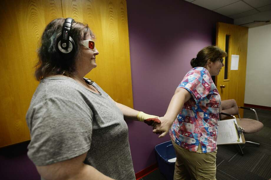 CNA Louise Zegelien of Midland, right, leads Robyn Zimmerman of Midland into a dark room where she will prepare to participate in a virtual simulation on what individuals with Dementia experience in their day to day lives on Wednesday, August 16, 2017 at The Arc of Midland. Photo: (Katy Kildee/kkildee@mdn.net)