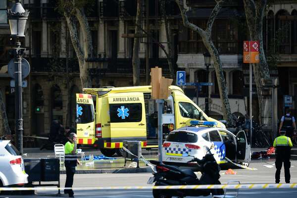 A policemen and a medical staff member stand past police cars and an ambulance in a cordoned off area after a van plowed into the crowd, injuring several persons on the Rambla in Barcelona on August 17, 2017.