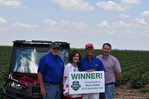 FiberMax grower Barry Street of Claytonville won the sweepstakes drawing for a Polaris Ranger XP 1000 ESP. He and his wife, SuDe Street, receive congratulations from Bayer Sales representative Stan Warren (left) and Southwest District Manager Dan Koch (right).