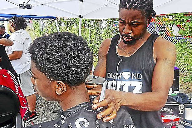 Diamond Cutz owner T.J. Green giving haircut to Jymere Jones at past rally.