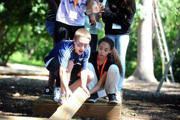 Rising Stamford High freshman Colin Richmond drops a plank on the ground during a team building exercise at Scalzi Park in Stamford, Conn. on Wednesday, August 16, 2017.