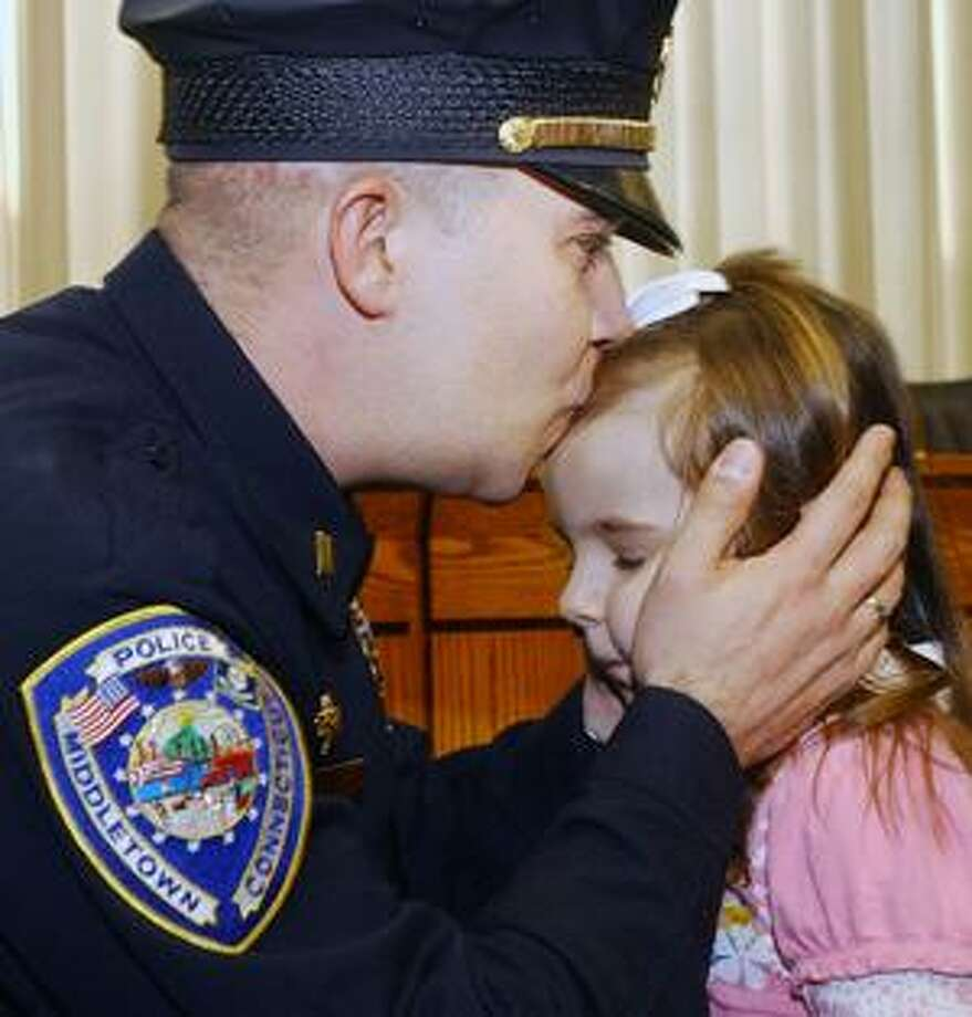 Middletown Police Lt. Chris Lavoie gives his 4-year-old daughter, Hailey, a kiss Friday after she pinned his new shield promoting him from sergeant to lieutenant at a swearing-in ceremony at the council chambers at Middletown City Hall. (Catherine Avalone