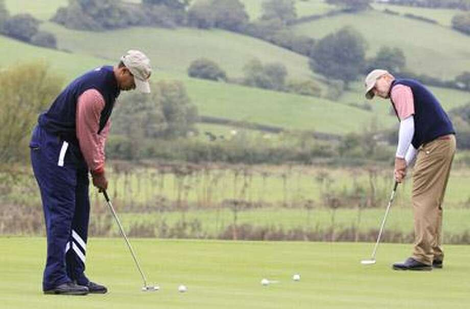 U.S. team members Tiger Woods, left, and Steve Stricker practice their putting prior to the 2010 Ryder Cup golf tournament at the Celtic Manor golf course in Newport, Wales, Thursday. (AP) Photo: ASSOCIATED PRESS / AP