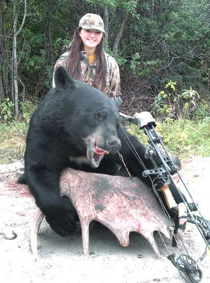 In this Aug. 2010 photo provided by the Olmstead family, Jessica Olmstead, 17, of Battle Creek, Mich., is shown with the 448-pound black bear she killed in Oba, Ontario, Canada. Olmstead killed the bear with a Matthews Passion bow and arrow set, designed for women, from a little over 16 yards away. The black bear was the young hunter's first big game take and she currently holds the Pope and Young Bowhunting record for the trophy bear.  (AP Photo/Olmstead Family photo) Photo: ASSOCIATED PRESS / Tim Olmstead