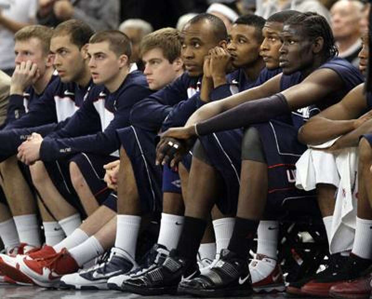 Connecticut players watch from the bench in the last minutes of Providence's 81-66 upset victory Wednesday night. (Associated Press)