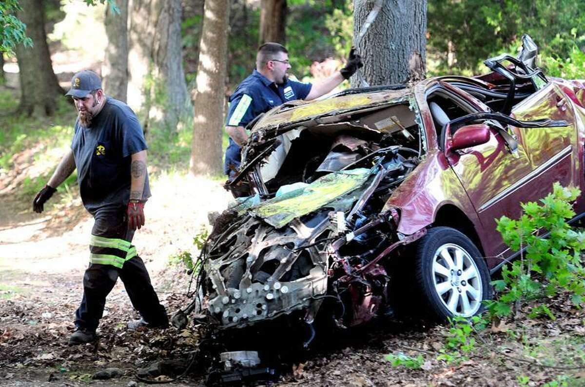 A car involved in a collision with a train lies down an embankment from the tracks near a private drive off of Herbert St. in Milford. (Arnold Gold/Register)