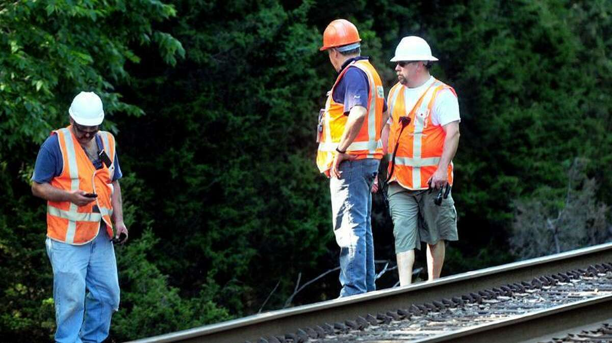 MTA personnel investigate an area of track where a car was hit by a train at a train crossing on a private drive off of Herbert St. in Milford. (Arnold Gold/Register)