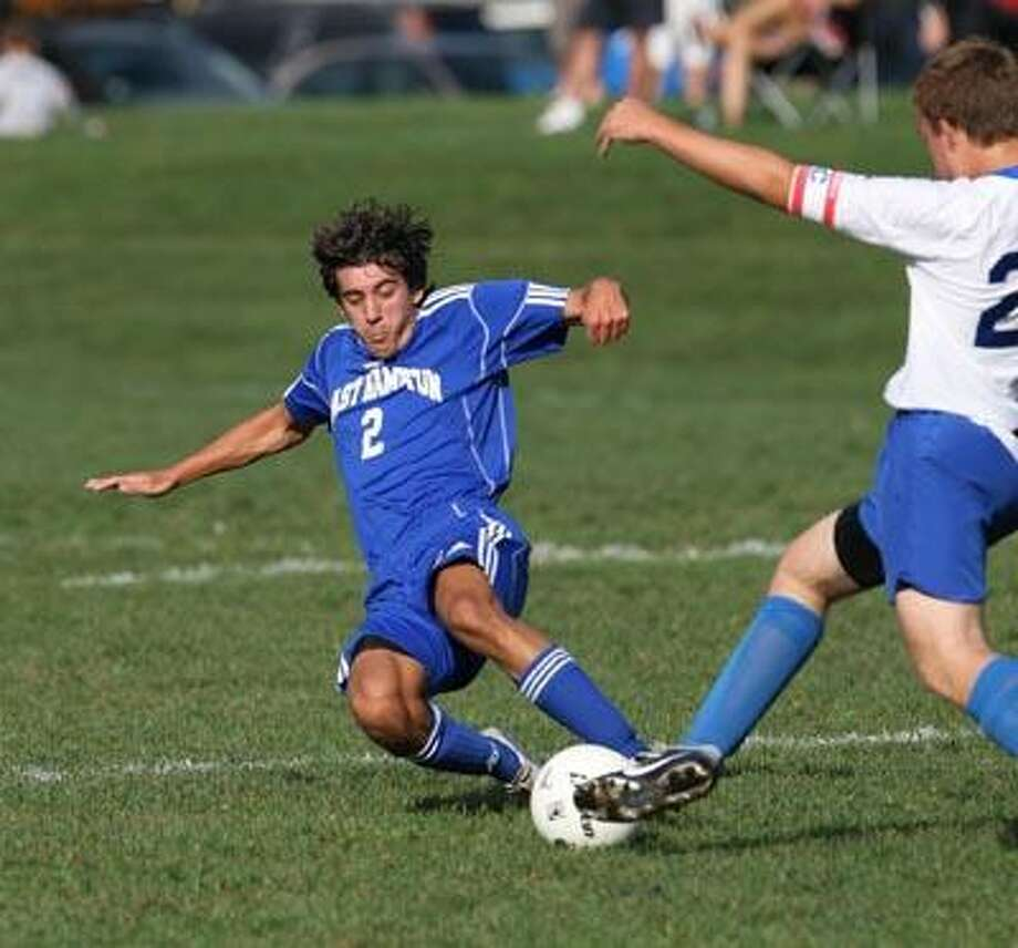 East Hampton's Seth Myers (2) attempts a slide tackle against Coginchaug's Eric Reilly Wednesday in Durham. (Todd Kalif
