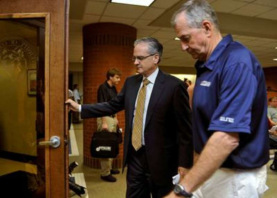 Connecticut basketball head coach Jim Calhoun, right, and Director of Athletics Jeff Hathaway leave a news conference in Storrs, Friday. The University says the NCAA has found eight violations in the school's men's NCAA college basketball program. (AP) Photo: AP / AP2010