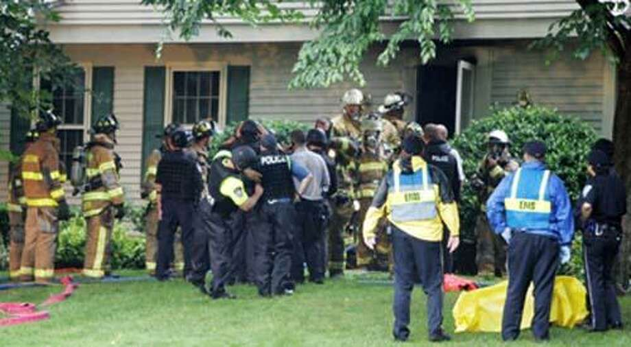 FILE (AP)- In this July 23, 2007 file photo,  law enforcement personnel work outside the home of  Dr. William Petit Jr., in Cheshire, Conn. Intruders broke into the home and held the family hostage for several hours before setting the house on fire. Dr. Petit was severely beaten, and his wife and two daughters were killed. A trial begins Monday, Sept. 13, 2010 in New Haven, Conn., Superior Court for Steven Hayes, one of two men charged with the crimes. Photo: ASSOCIATED PRESS / Meriden Record Journal