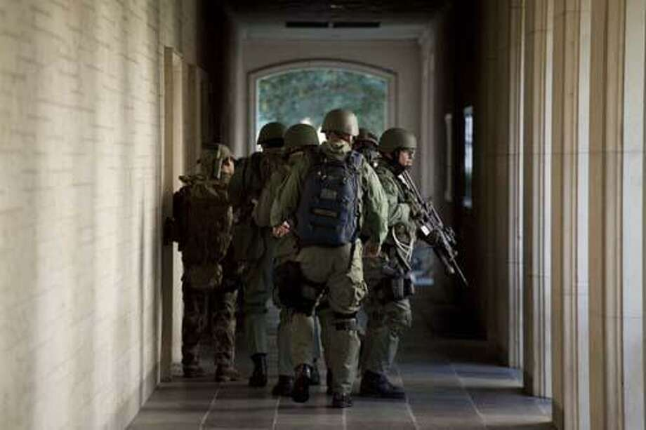 AP- Police prepare to enter Calhoun Hall at the University of Texas at Austin campus in Austin, Texas on Tuesday, Sept. 28, 2010. A gunman opened fire Tuesday inside the Perry-Castaneda Library, then fatally shot himself, and police are searching for a possible second suspect, university police said. Photo: AP / Tamir Kalifa
