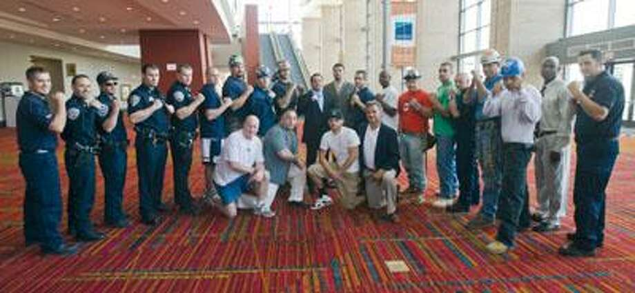 Members of the Middletown Police department, Middletown Fire Department and Union of Workers pose with other boxing participants and Lions Den owner Doug Cartelli and vice president of operations, Craig Salamone at a press conference Thursday announcing the June 26th boxing event at the Connecticut Convention Center in Hartford to raise money for the families of the Kleen Energy Plant explosion victims. (Rachel Simspon / Special to the Press)
