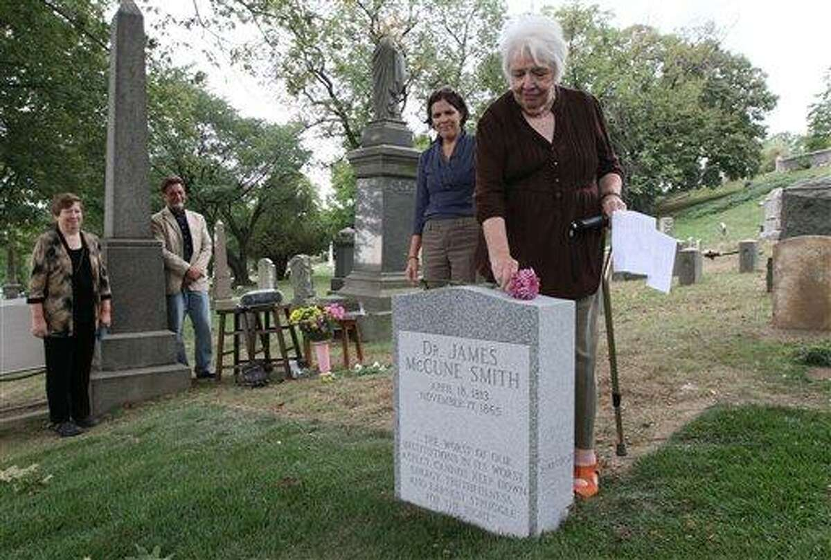 Antoinette Martignoni, right, places a flower atop the new tombstone of her great-grandfather Dr. James McCune Smith, the nation's first professionally trained African-American doctor, as Martignoni's daughter, Elizabeth Strazar, second from right, looks on during a ceremony honoring Smith, Sunday Sept. 26, 2010 at Cypress Hills Cemetery in the Brooklyn borough of New York. Smith's gravesite had been unmarked since his death in 1865. Standing left is Smith's great-great-granddaughter Judy Gerlitz. (AP Photo/Tina Fineberg)