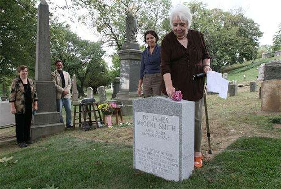 Antoinette Martignoni, right, places a flower atop the new tombstone of her great-grandfather Dr. James McCune Smith, the nation's first professionally trained African-American doctor, as Martignoni's daughter, Elizabeth Strazar, second from right, looks on during a ceremony honoring Smith, Sunday Sept. 26, 2010 at Cypress Hills Cemetery in the Brooklyn borough of New York.  Smith's gravesite had been unmarked since his death in 1865. Standing left is Smith's great-great-granddaughter Judy Gerlitz. (AP Photo/Tina Fineberg) Photo: AP / FR73987 AP