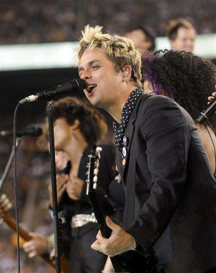 "FILE - In this Sept. 13, 2010 file photo, Billie Joe Armstrong of Green Day performs with cast members of the Broadway musical ""American Idiot"" at halftime during an NFL football game between the New York Jets and the Baltimore Ravens at New Meadowlands Stadium in East Rutherford, N.J. Green Day front man Billie Joe Armstrong is joining the cast of ""American Idiot,"" the Broadway show he helped create based on the band's 2004 Grammy-winning album, The Associated Press reported Sunday, Sept. 26, 2010. (AP Photo/Henny Ray Abrams, File) Photo: ASSOCIATED PRESS / FR151332 AP"