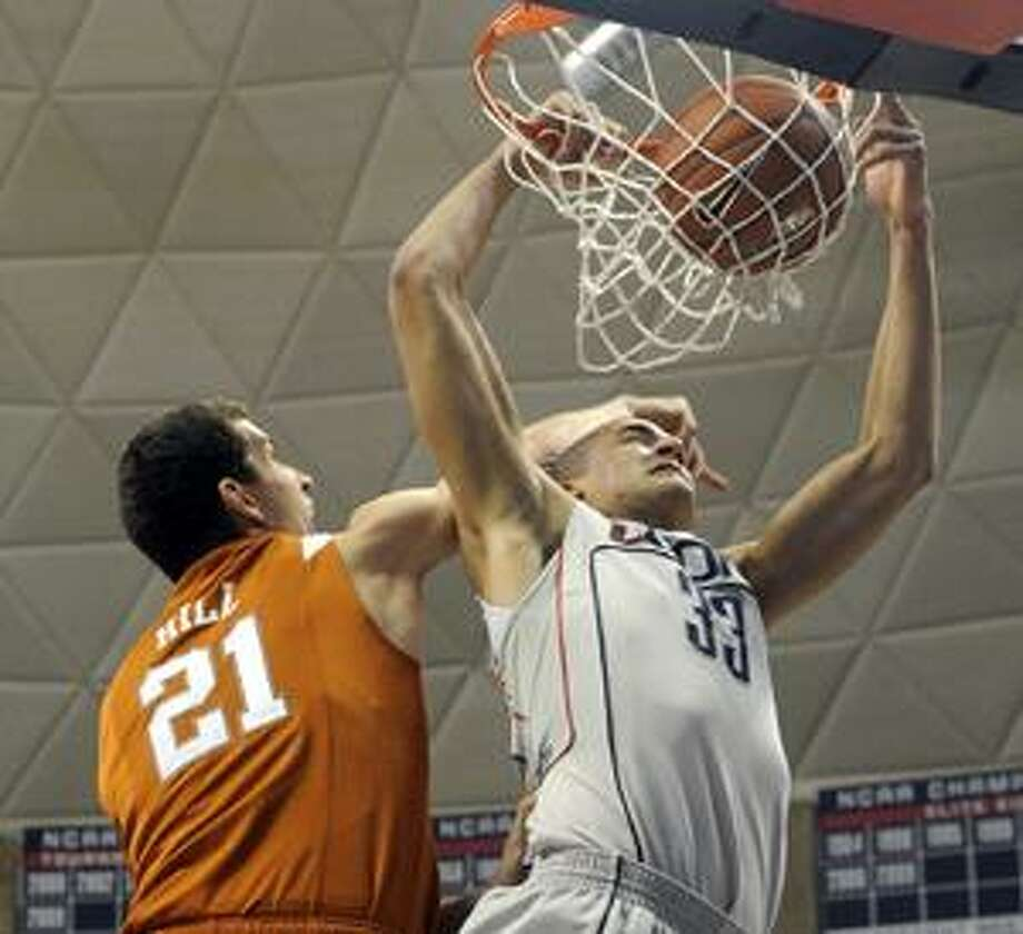 Texas's Matt Hill, left, fouls Connecticut's Gavin Edwards during the first half of their NCAA men's college basketball game in Storrs on Saturday (AP Photo/Fred Beckham). Photo: ASSOCIATED PRESS / AP2010