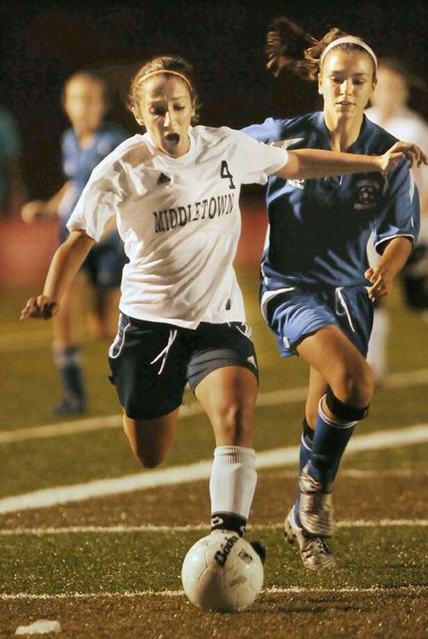 Middletown junior forward Ava Delmastro breaks past Plainville defender Megan Dixon during a match at Rosek-Skubel Stadium in Middletown. The Blue Dragons were defeated 1-0. (Catherine Avalone / TheMiddletownPress