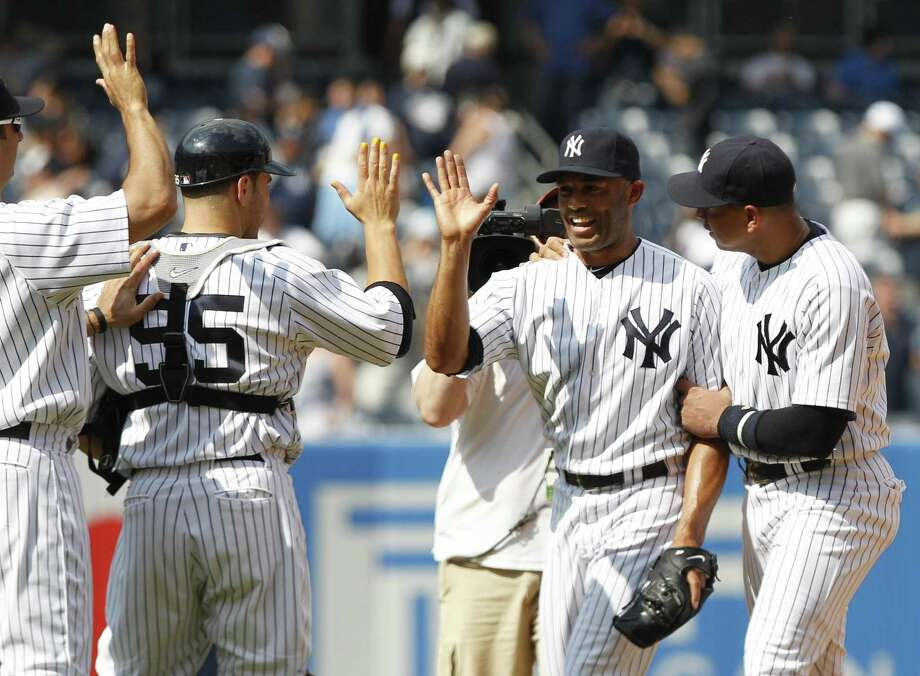 New York Yankees players, from right, Alex Rodriguez, Mariano Rivera and Russell Martin (55) celebrate after a baseball game against the Toronto Blue Jays Wednesday, May 25, 2011, at Yankee Stadium in New York. Rivera has become the first pitcher in major league history to have appeared in 1,000 games for one team and the 15th to reach the plateau overall. The Yankees won the game 7-3. (AP Photo/Frank Franklin II) Photo: ASSOCIATED PRESS / AP2011
