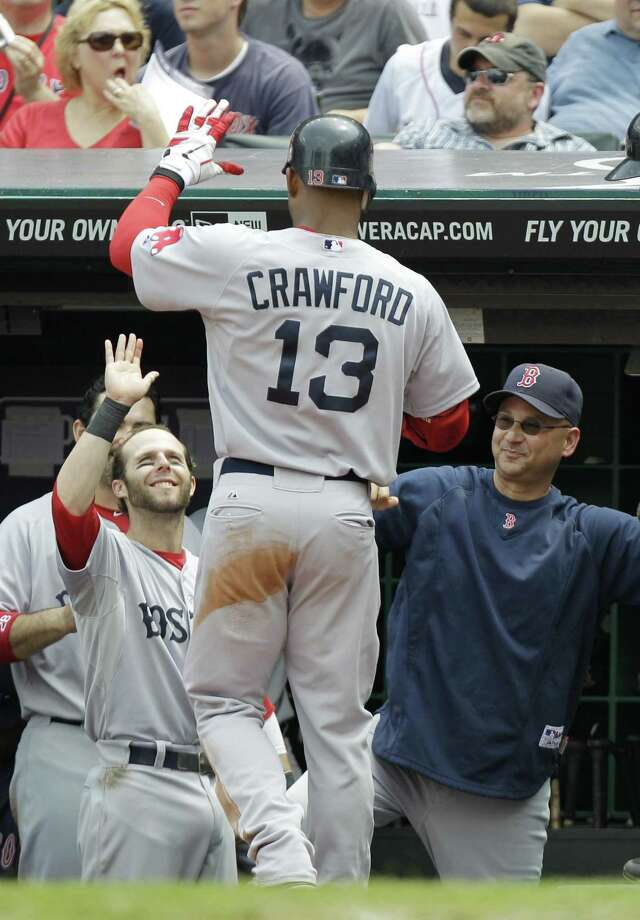 Boston Red Sox's Carl Crawford (13) is greeted at the dugout by manager Terry Francona, right, and Dustin Pedroia after hitting a solo home run in the fourth inning baseball game against the Cleveland Indians, Wednesday, May 25, 2011, in Cleveland. (AP Photo/Mark Duncan) Photo: ASSOCIATED PRESS / AP2011