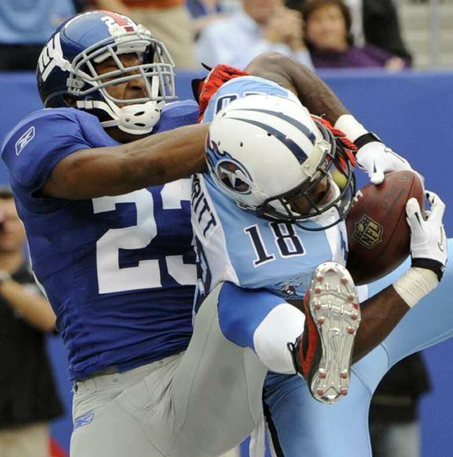 Tennessee Titans wide receiver Kenny Britt (18) catches a touchdown pass as New York Giants cornerback Corey Webster (23) defends during the third quarter of an NFL football game at New Meadowlands Stadium Sunday in East Rutherford, N.J. (AP Photo/Bill Kostroun) Photo: AP / FR59151 AP