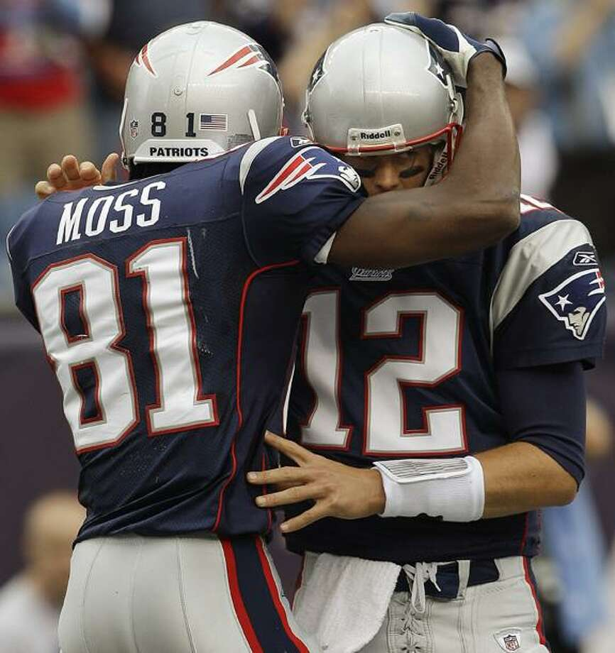 New England Patriots quarterback Tom Brady (12) hugs wide receiver Randy Moss (81) after they connected for Moss' second touchdown-reception of the day during the third quarter of an NFL football game against the Buffalo Bills in Foxborough, Mass., Sunday. The Patriots defeated the Bills 38-30. (AP Photo/Stephan Savoia) Photo: AP / AP